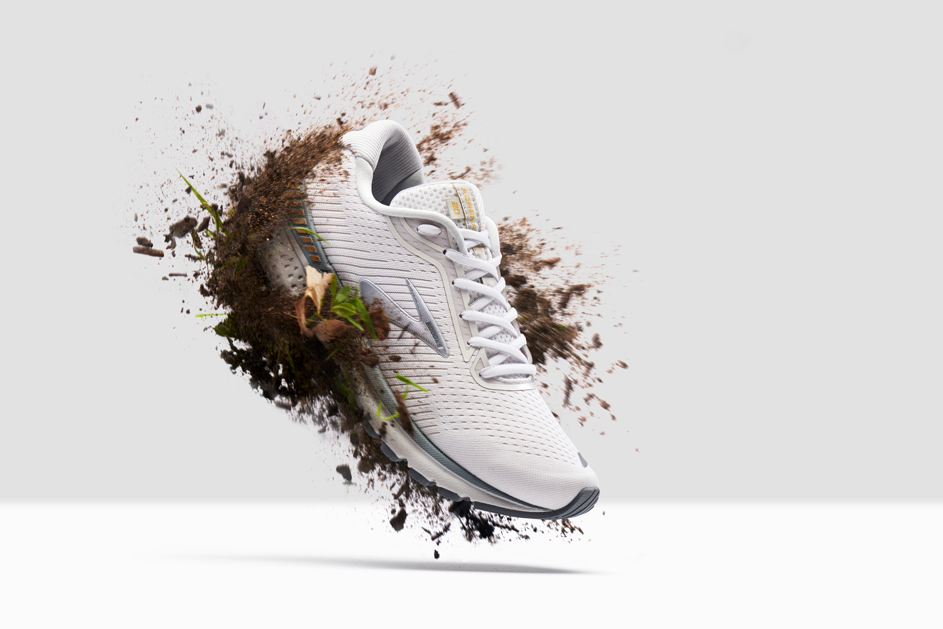 Brooks Trail Running Shoe hovering with dirt splashing, by still life photographer Adrian Mueller New York
