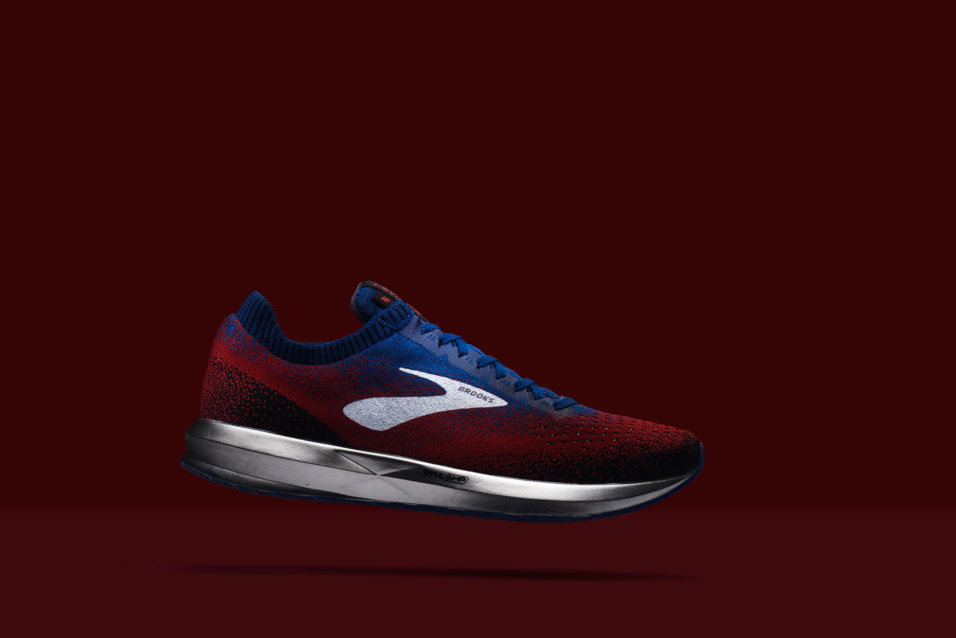 Brooks Street Running Shoe hovering above red surface, by still life photographer Adrian Mueller New York