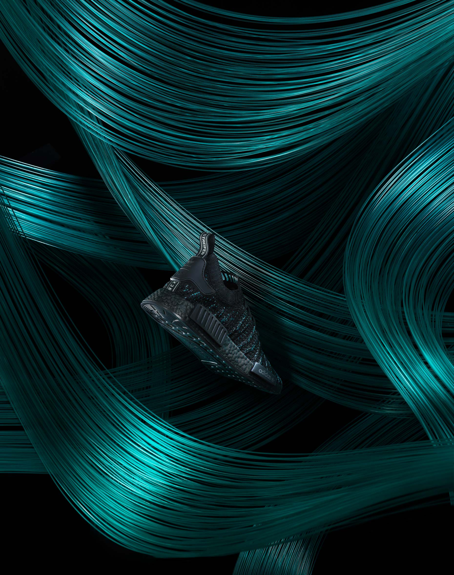 Adidas Parley shoe in front of hundreds of strings of green thread, photographed by product and still life photographer Adrian Mueller New York
