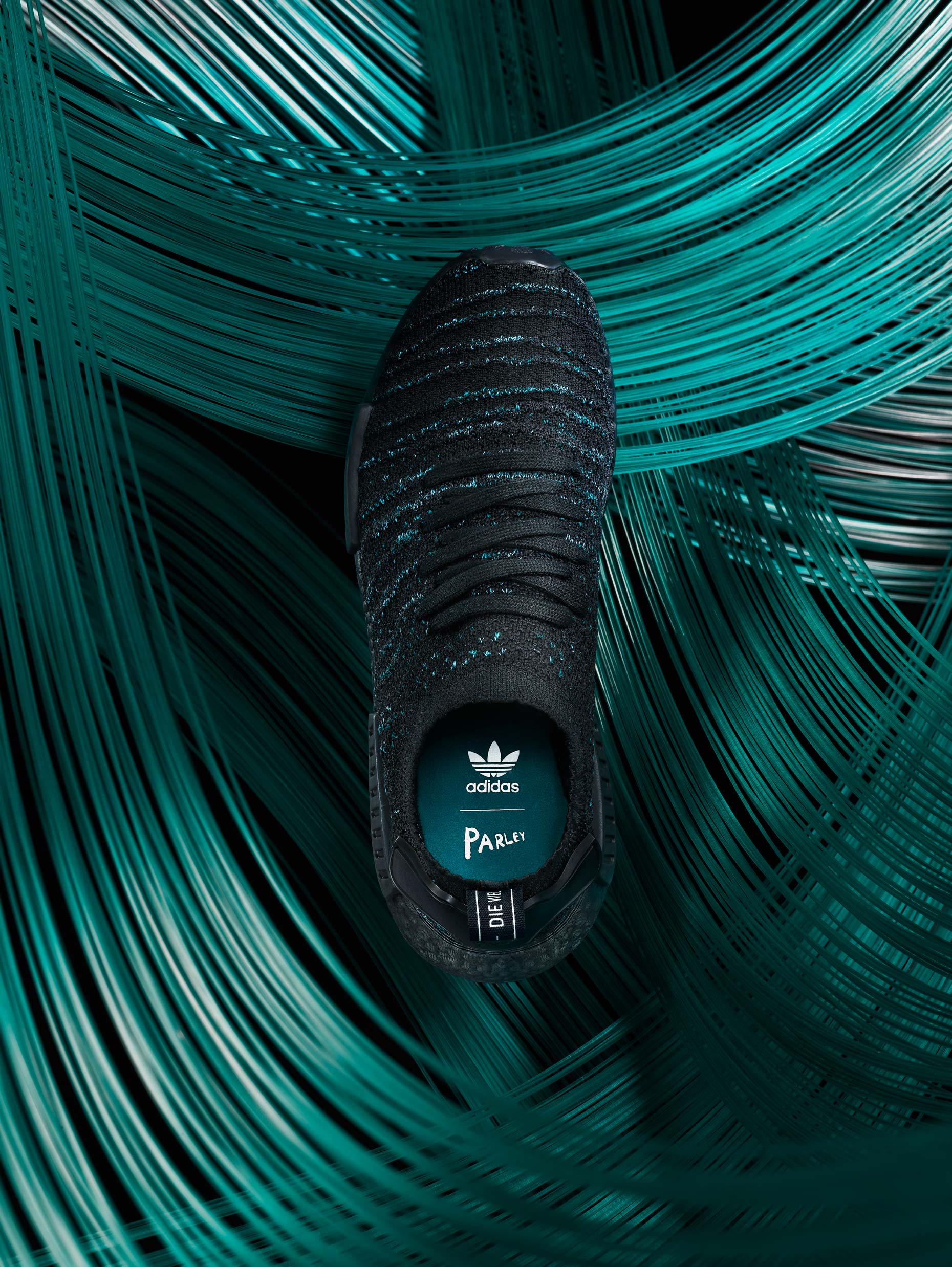 Adidas Parley shoe standing straight up in front of hundreds of strings of green thread, photographed by product and still life photographer Adrian Mueller New York