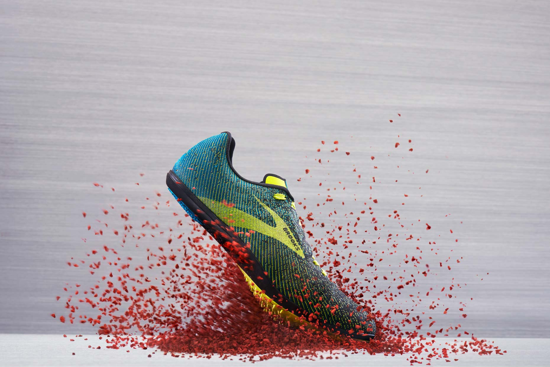 Brooks Track Running Shoe on a red track, by still life photographer Adrian Mueller New York