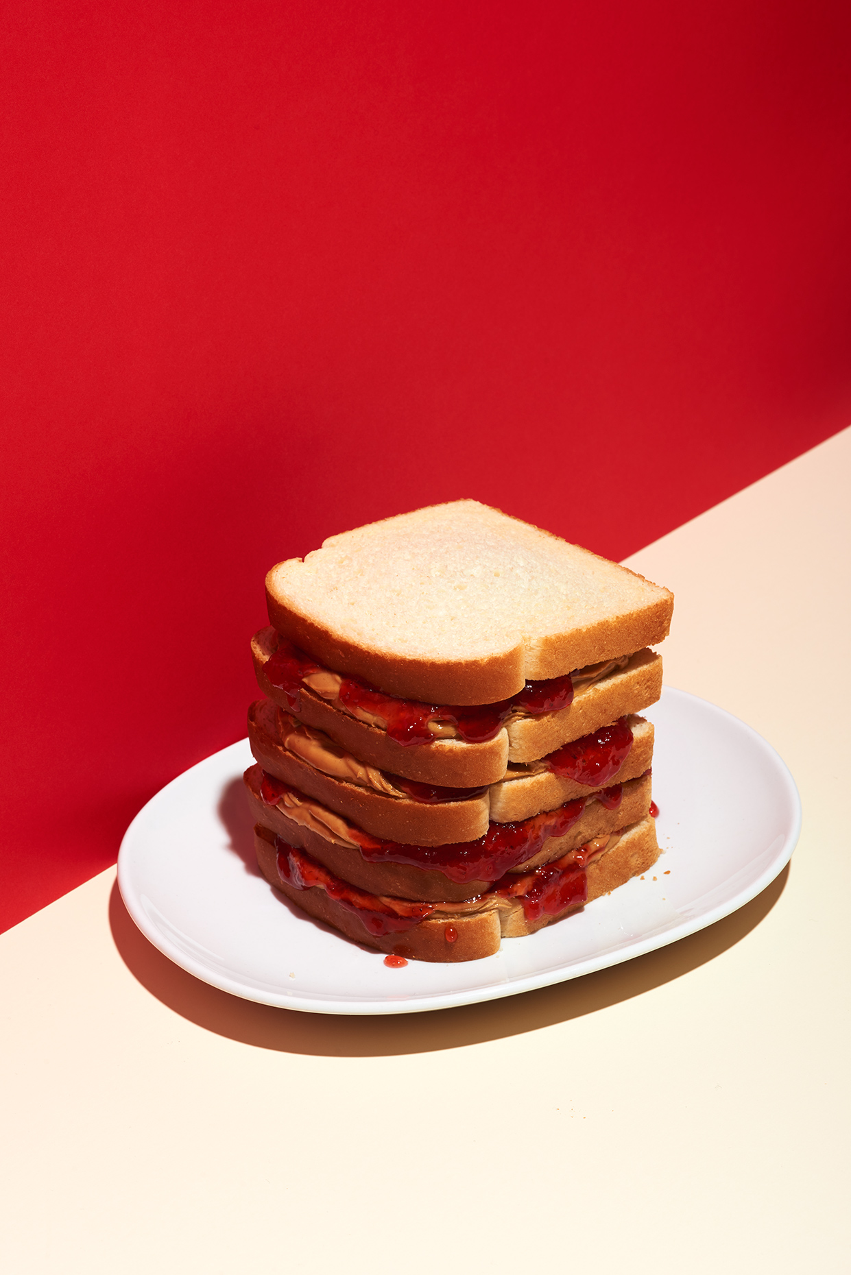 Peanut Butter & Jelly Sandwich on red and white, photographed by New York Food Photographer Adrian Mueller