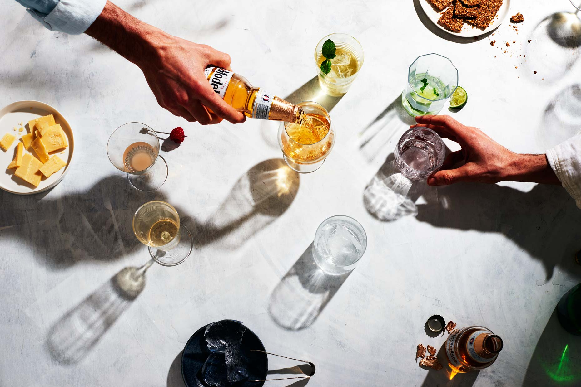 Hand pouring beer into glass on big table with drinks, photo by Food and Beverage Photographer Adrian Mueller New York