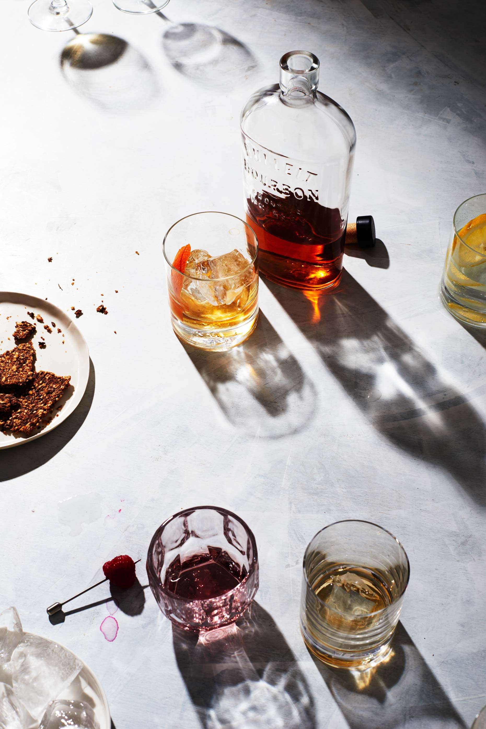 Glass of bourbon next to bottle and other drinks on white surface, photo by Food and Beverage Photographer Adrian Mueller, New York