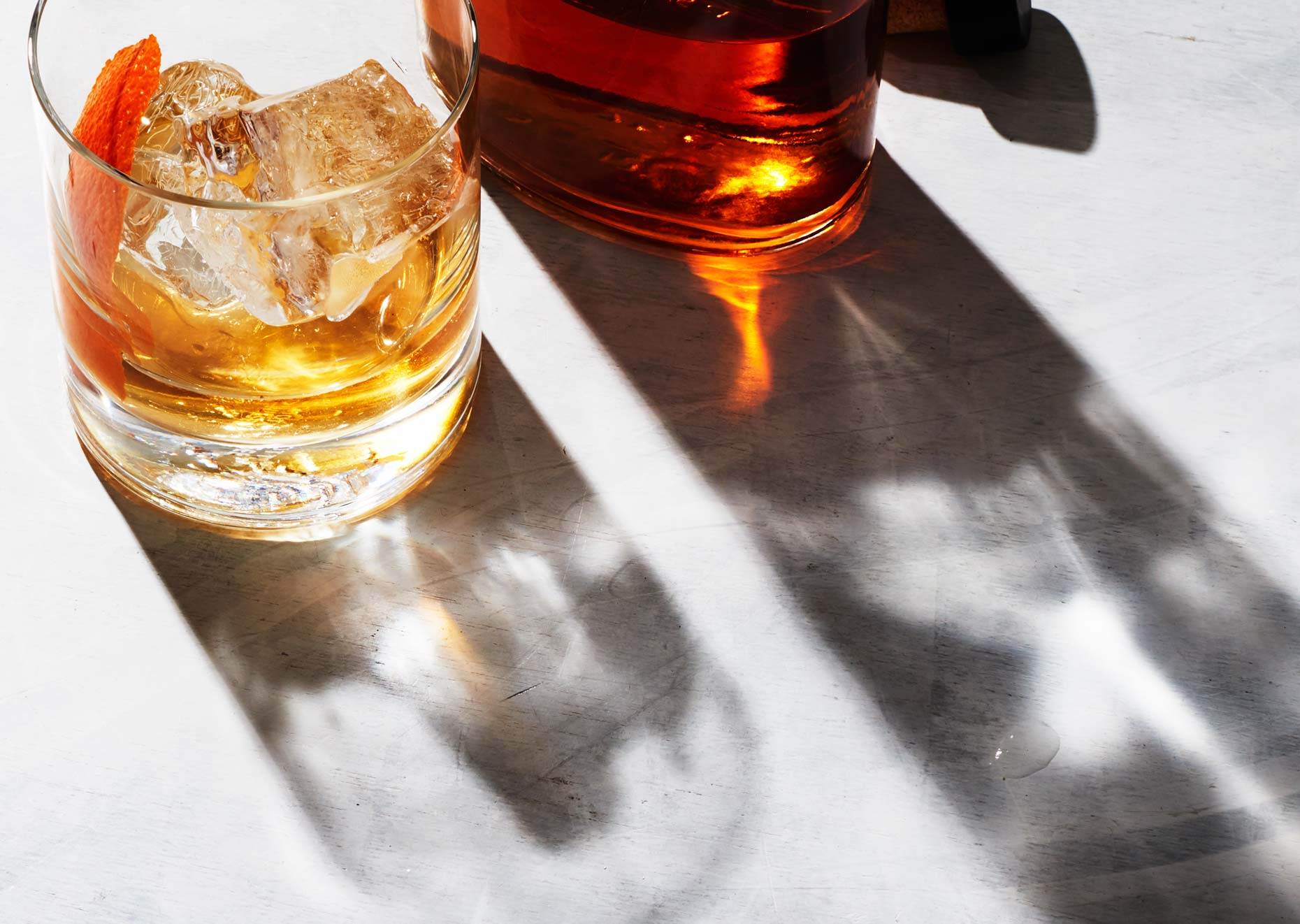Glass of bourbon next to bottle on white surface, photo by Food and Beverage Photographer Adrian Mueller, New York