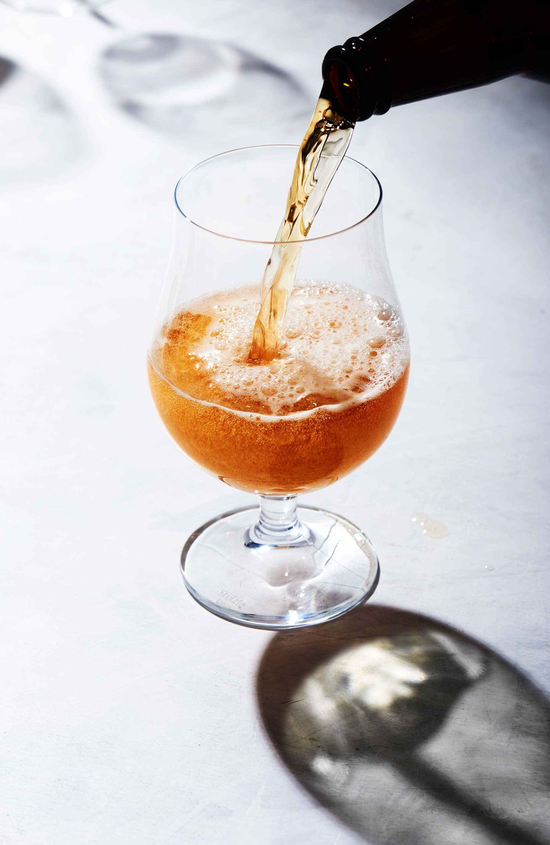 Glass of beer being poured on a white surface, shot from the side by Food and Beverage Photographer Adrian Mueller, New York