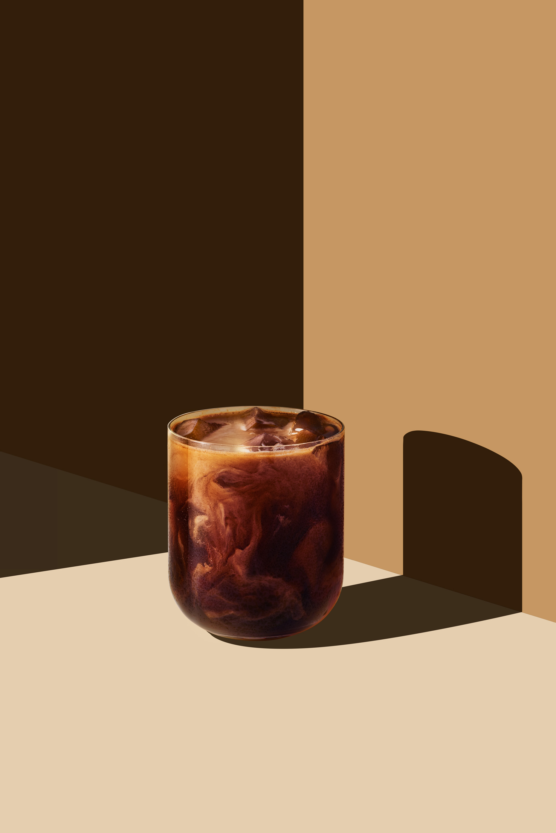 Iced coffee with milk swirls on colorful background, by Food and Beverage photographer New York Adrian Mueller