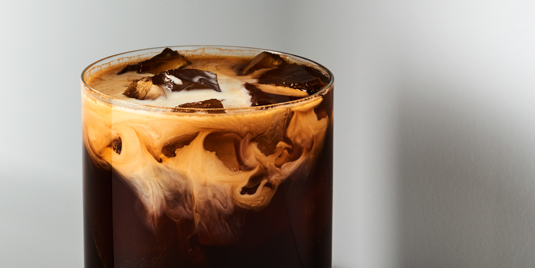 Iced coffee with milk swirls on gray background, photo by Adrian Mueller New York Food and Beverage photographer